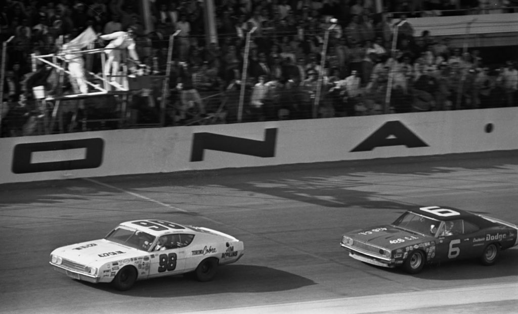 #98 LeeRoy Yarbrough takes the checkered flag just ahead of #6 Charlie Glotzbach to win the 1969 Daytona 500. Yarbrough took a softer compound tire on his final stop and was able to run down Glotzbach and slingshot past him on the final lap to win the race.
